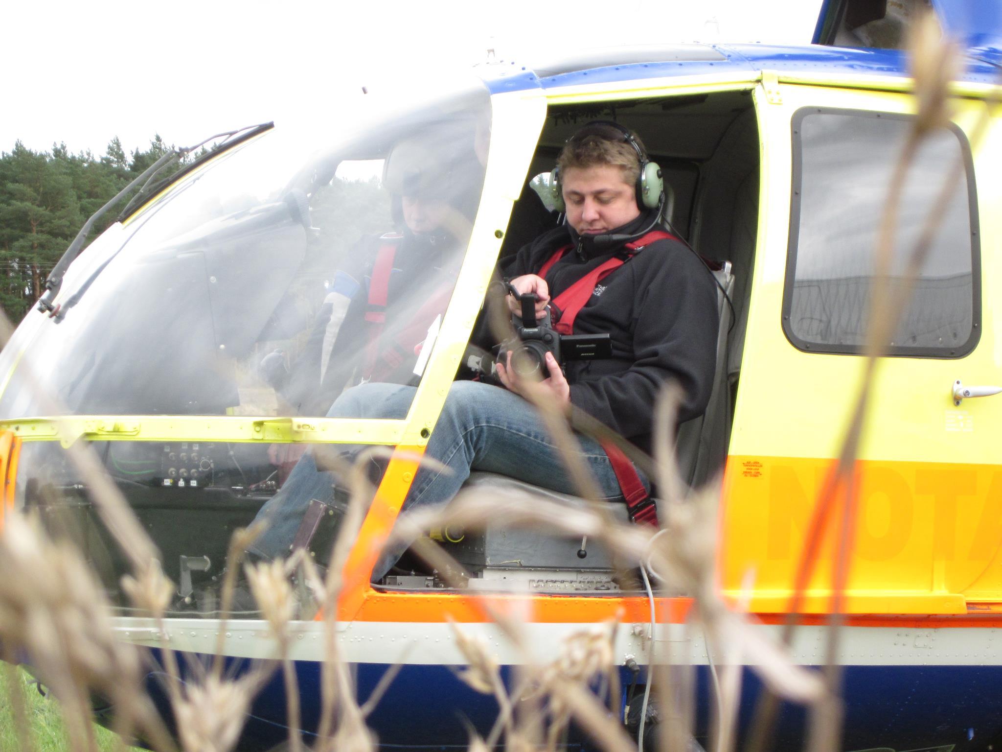 Kameramann Daniel Klahr macht sich für die Luftaufnahme aus dem Helikopter bereit.